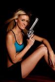 Woman blue halter gun black smile — Stock Photo