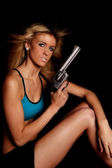 Woman blue halter top gun serious — Stock Photo