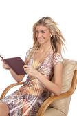Donna in poltrona con un libro alla ricerca — Foto Stock