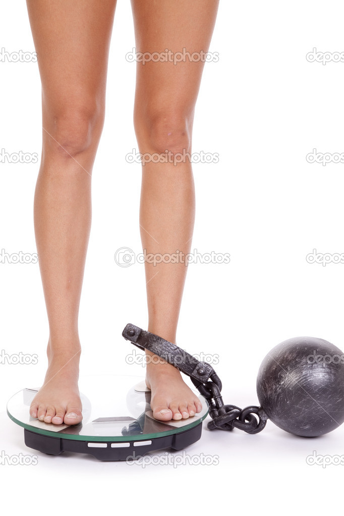 A woman has a ball and chain on her leg and standing on the scales. — Stock Photo #12094098