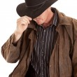 Cowboy leaning over touching hat — Stock Photo #12101767