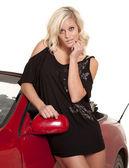 Schwarzes kleid von rotes auto stehen — Stockfoto