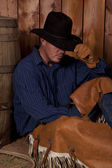 Cowboy hold hat sit barrel — Stock Photo