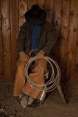 Cowboy sitting on barrel head down — Stock Photo
