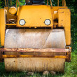 Abandoned road roller machine in green bushes — Stock Photo