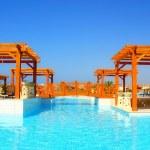 Luxury swimming pool and pergola in resort hotel — Stock Photo