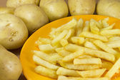 Raw potatoes and chips — Stock Photo