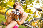 Beautiful young woman playing with a vintage camera — Stock Photo