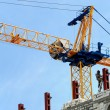 Stock Photo: Crane builds a house