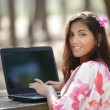 Woman using laptop outdoors — Stock Photo