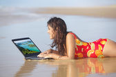 Woman using laptop on beach — Stock Photo