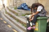 Sad drunk homeless woman on bin — Stock Photo