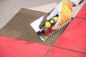 Worker with notched trowel install red tiles with tile adhesive — Stock Photo