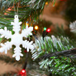 Christmas snow flake on a christmas tree — Stock Photo