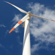 Wind mill power generator against a cloudy blue sky — Stock Photo