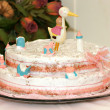 Baptism cake with small figurines and a stork on top — Stock Photo