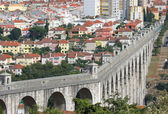 City landscape with several buildings houses and an aqueduct — Stock Photo