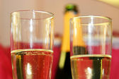 Two champagne glasses with bottle on background — Stock Photo