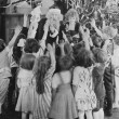 Santa Claus with group of excited children — ストック写真