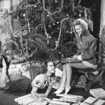 Teenage girls with presents and Christmas tree — Stock Photo