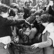 Children crowded around apple bobbing — Stock Photo