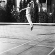 Male tennis player jumping for shot — Foto de Stock
