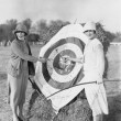 Stock Photo: Women with bulls eye in archery target