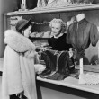Customer and clerk in clothing store — Stock Photo