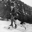 Man hunting in snowy mountains with dog — Foto Stock