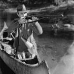 Man aiming gun from canoe — Stock Photo