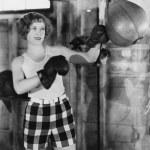 Female boxer using punching bag — Stock Photo