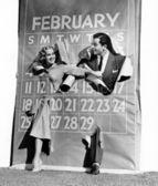Couple bursting through leap year calendar — Stock Photo