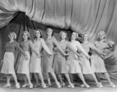 Portrait of line of female dancers on stage — Stockfoto