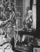 Genç çocuk noel ağacı ve hediyeler penceresinden hayran — Stok fotoğraf