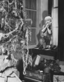 Jeune garçon, admirer l'arbre de noël et des cadeaux de fenêtre — Photo