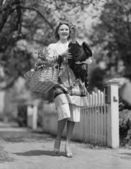 Woman carrying live turkey and grocery basket — Stock Photo