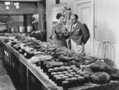 Casal com mesa coberta em alimento para a refeição do feriado — Foto Stock