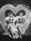 Portrét dvou žen sedí ve velké srdce — Stock fotografie