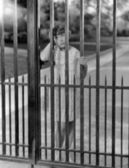 Portrait of girl through bars of fence — Stock Photo