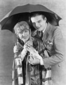 Portrait of couple under umbrella — Stock Photo