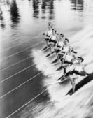 Row of women water skiing — ストック写真