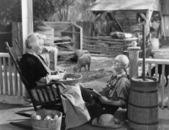 Elderly couple on porch of farmhouse — Stok fotoğraf