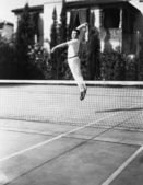 Male tennis player jumping for shot — Stock Photo
