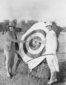 Women with bulls eye in archery target — Stock Photo