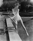 Mujer sumergir los pies en la piscina al aire libre — Foto de Stock