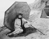 Woman with umbrella at beach — Stock Photo