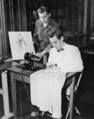 Young men using sewing machine — Stock Photo