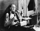 Man with typewriter talking on phone — ストック写真