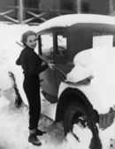 Woman shoveling snow off car — Stock Photo