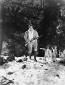 Man jacht in besneeuwde bossen met honden — Stockfoto